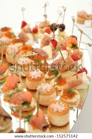 Various meat, fish and cheese banquet snacks on banquet platter - stock photo