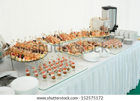 Various meat, fish and cheese banquet snacks on banquet table, catering event - stock photo