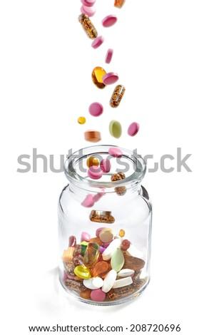 various medical pills falling into glass jar, selective focus - stock photo