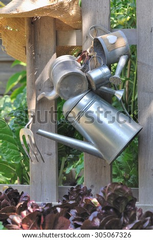 various metal watering cans hung on a fence in garden - stock photo