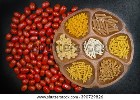 Various mix of pasta on wooden bowl, small red tomatoes, diet and food concept on black background. - stock photo
