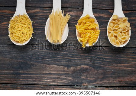 Various mix of pasta on wooden rustic background, sack and wooden spoons.  - stock photo