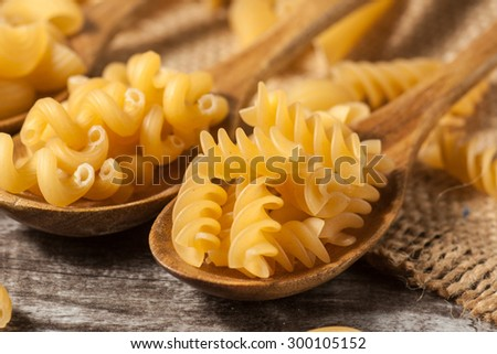Various mix of pasta on wooden rustic background, sack and wooden spoons. Diet and food concept. - stock photo