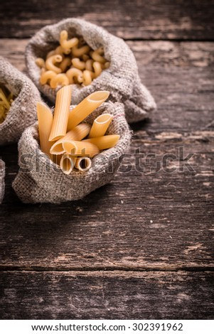 Various mix of pasta on wooden rustic background, sack and wooden spoons.et and food concept.