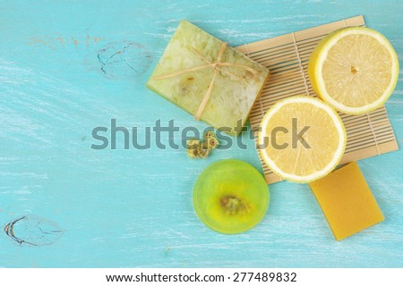 Various natural soaps and lemon on aquamarine wooden background. Top view point. - stock photo