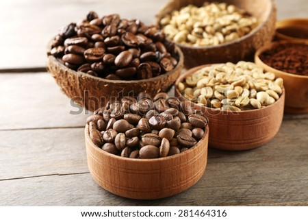 Various of coffee in small dishes on wooden table, closeup - stock photo