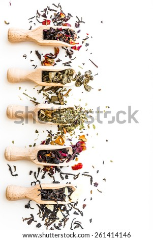 Various of dried tea in wooden scoops on white  table