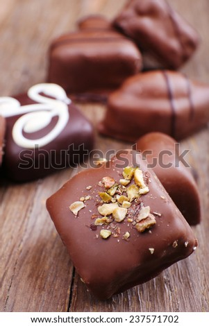 Various of sweet candy on wooden textured background with chocolate heart foreground - stock photo