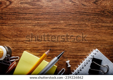 Various Office or School Stuffs, Such as Notes, Paper, Pen, Pencil and Clips, on Textured Wooden Table, Captured at the Bottom Frame, with Text Area on the Top. - stock photo
