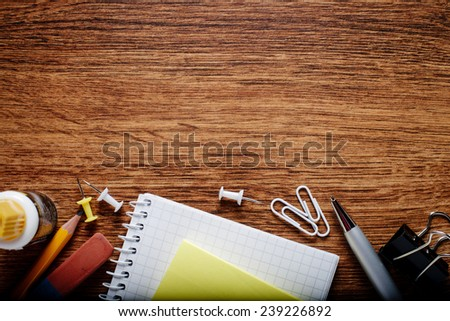 Various Office Supplies on Wooden Table, Captured at the Bottom Edge of the Frame, with Copy Space on Top for Texts. - stock photo