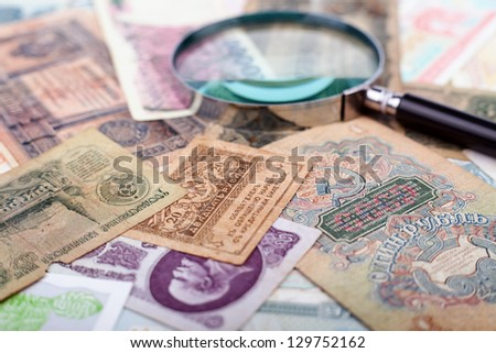 Various old russian paper money, magnifying glass