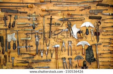 Various old tools on the wall in leather craft workshop ...