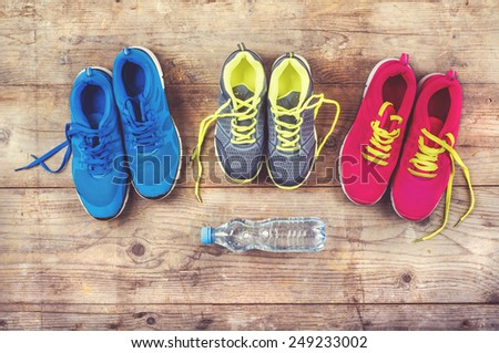 Various pairs of colorful sneakers laid on the wooden floor background - stock photo