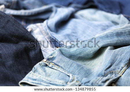 Various pairs of jeans pants scattered in chaos.