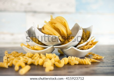 Various pasta in small bowls with mix of pasta on wooden table - stock photo