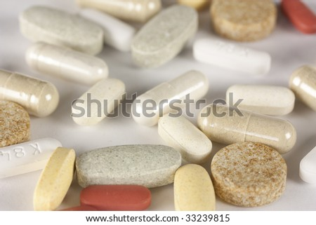 Various pills on a blank background - stock photo
