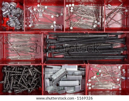 Various pins nails and staples in red container