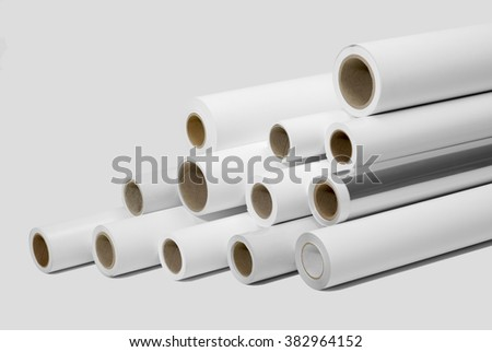 various print media rolls for wide-format printers in light grey back - stock photo