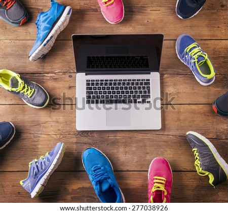 Various running shoes and notebook laid on a wooden floor background - stock photo