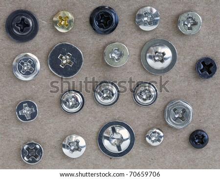 Various screws head on  cardboard  background - stock photo