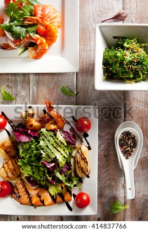 Various Seafood Salad on Wooden Background - stock photo