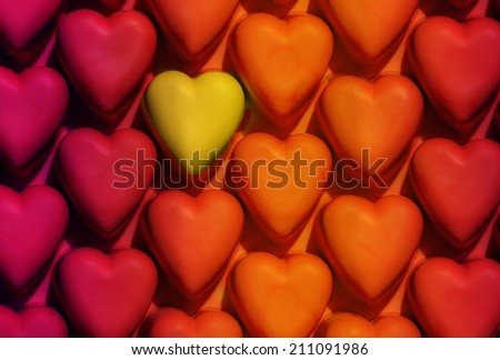 various shades of red and orange hearts pattern with one yellow isolated heart - stock photo