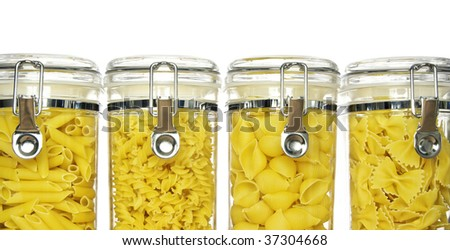 Various shapes of pasta in jars: fusilli (spirals), penne, farfalle (bow tie), conchiglie (shells) on white background - stock photo