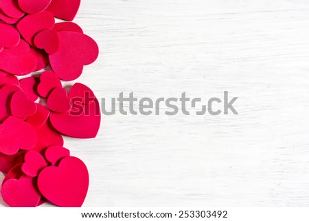 Various size valentine's day hearts on white wooden background. Copy space background. - stock photo