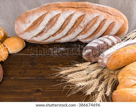 Various sized whole loaves of freshly baked artisan bread next to wheat stalks on dark wooden table with empty area for other objects - stock photo