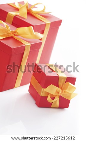 Various sizes red gift boxes with gold ribbon. All on white background.  - stock photo