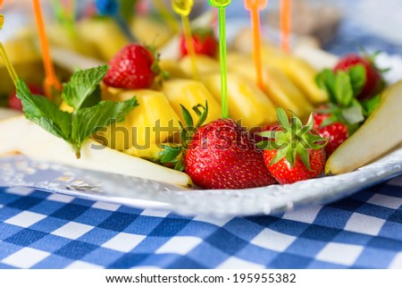 Various sliced fruits on plate on napkin close-up - stock photo
