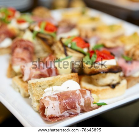 Various snacks in plate on banquet table - stock photo