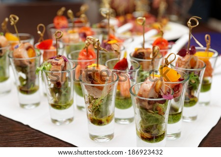 Various snacks in shot glasses on table - stock photo