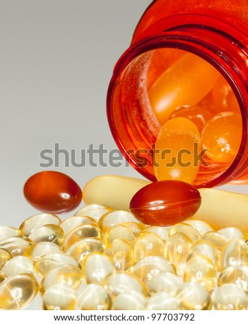 Various sorts of fish oil tablets spilling from prescription bottle onto table - stock photo