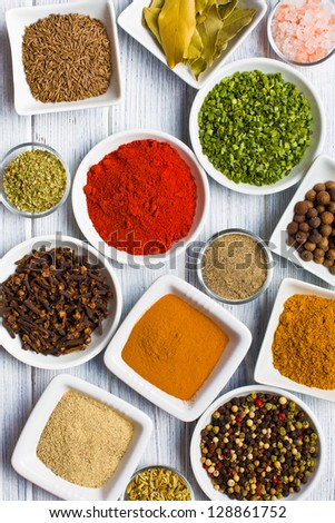 Various spices and herbs on wooden table. - stock photo