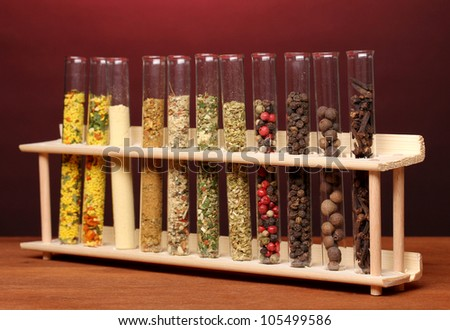 Various spices in tubes on wooden table on red background - stock photo