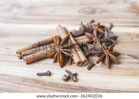 Various spices on a wooden background. Anise star, cinnamon sticks and cloves on a wooden background. Selective focus. - stock photo