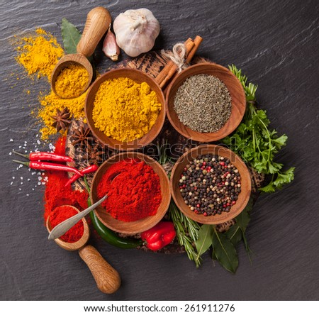 Various spices on black stone shot from aerial view - stock photo