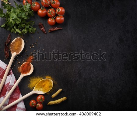 Various spices on rustic black background with copyspace.