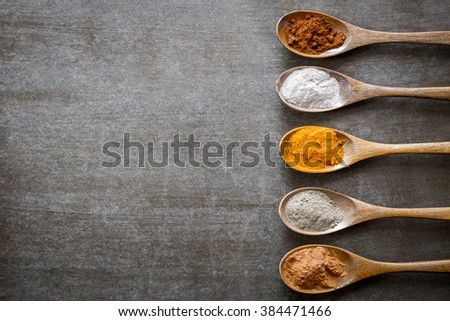 Various spices on wooden spoons. Food ingredients. - stock photo