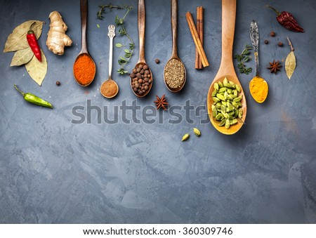 Various Spices powder turmeric, cardamom, chili, paprika, ginger, star anise and clove at blue stone grunge background. Free space for your text