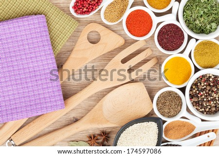 Various spices selection and kitchen utensils on wooden table - stock photo