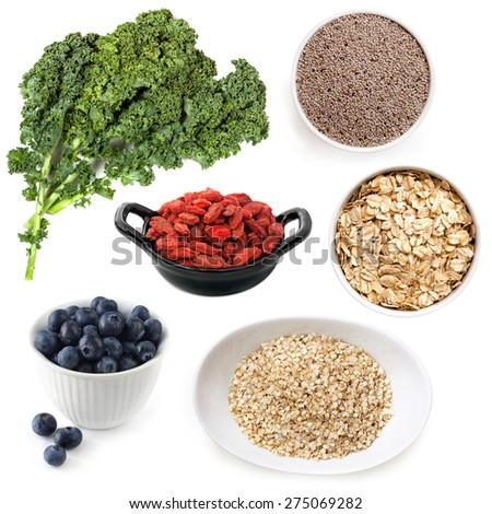 Various superfoods isolated on white.  Includes kale, chia seeds, goji berries, blueberries, oats and quinoa. - stock photo
