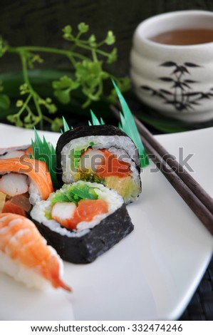 various sushi on white plate with japanese hot tea on background