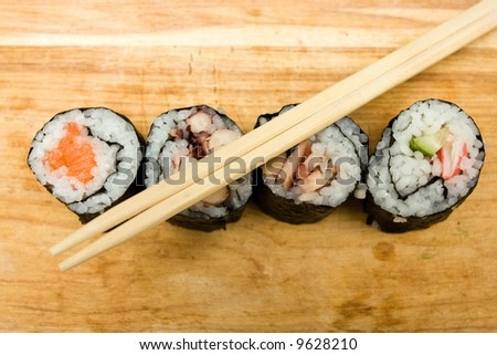 Various sushi rolls on cutting board with chopsticks. - stock photo