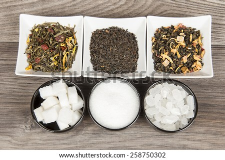 Various tea and various kind of sugar on wooden table - stock photo