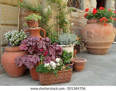 various traditional clay planters with decorative plants on italian narrow street,Europe - stock photo