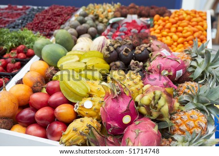 Various tropical fruits and berries lying on market stall - stock photo