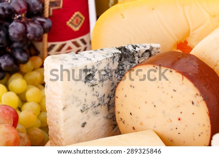 Various type of cheese and grapes closeup picture. - stock photo