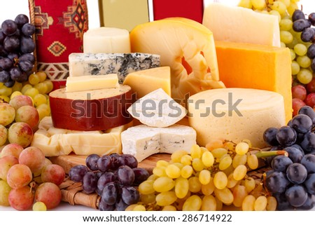 Various type of cheese,wines and grapes on wooden board closeup picture. - stock photo
